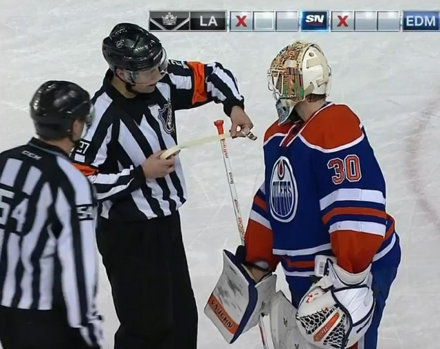 Referee Eric Furlatt applies approved white tape over Scrivens' illegally-colored knob