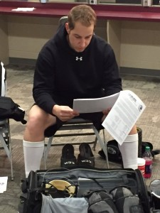 Tarnaris reads over game notes from each team. (Image: Ted Warren)